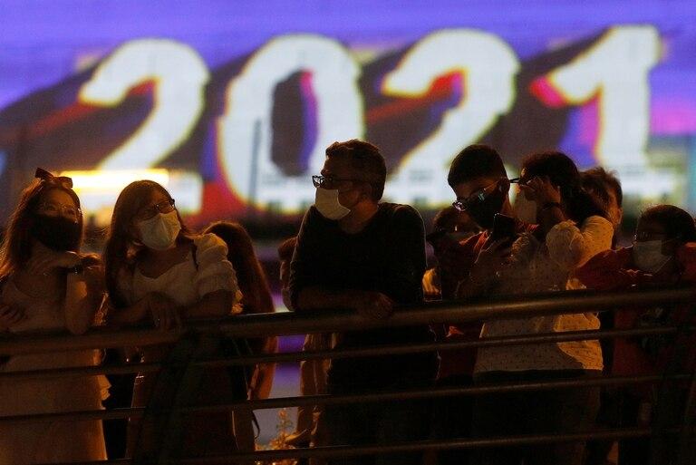 La gente observa después de la cuenta regresiva para el Año Nuevo, ya que los tradicionales fuegos artificiales de Nochevieja se cancelan debido al brote de la enfermedad por coronavirus (COVID-19), en Marina Bay en Singapur