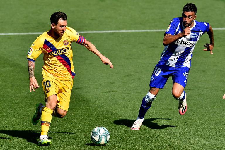 Barcelonas Lionel Messi, left, fights for the ball with Alaves Victor Camarasa during the Spanish La Liga soccer match between Alaves and FC Barcelona, at Mendizorroza stadium, in Vitoria, northern Spain, Sunday, July 19, 2020