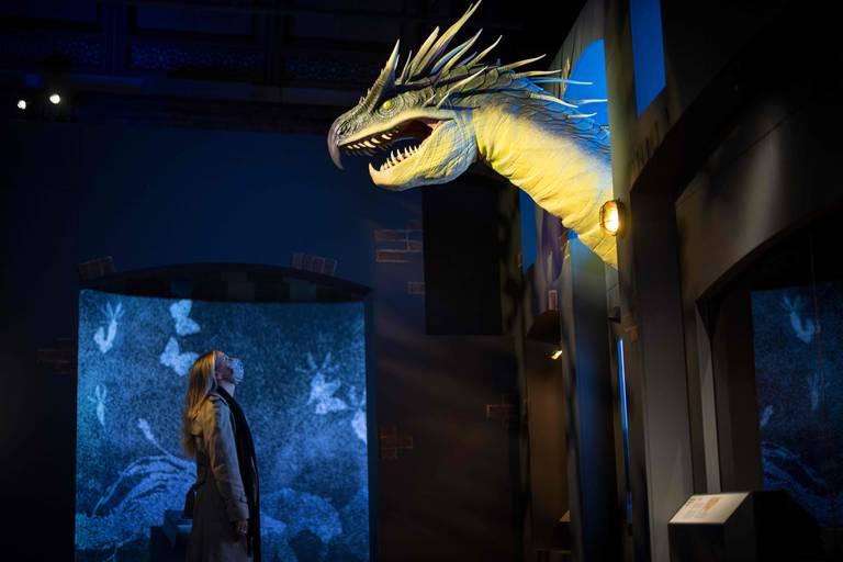 Un integrante del staff del museo de Londres frente un dragón de la saga de bestias fantásticas